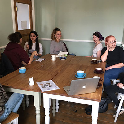 Photo of a group of people talking in a coffee shop