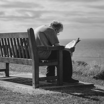 Photo of an older man sitting on a bench by the sea reading a paper