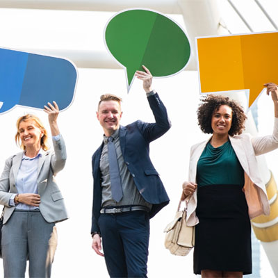 Photo of three people holding up speech bubble graphics